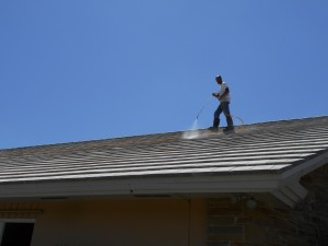 Man using power washer on roof of home.